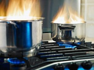 Cooking pots on fire on top of a stove