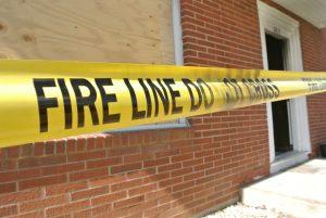 fire line tape across brick building after a fire