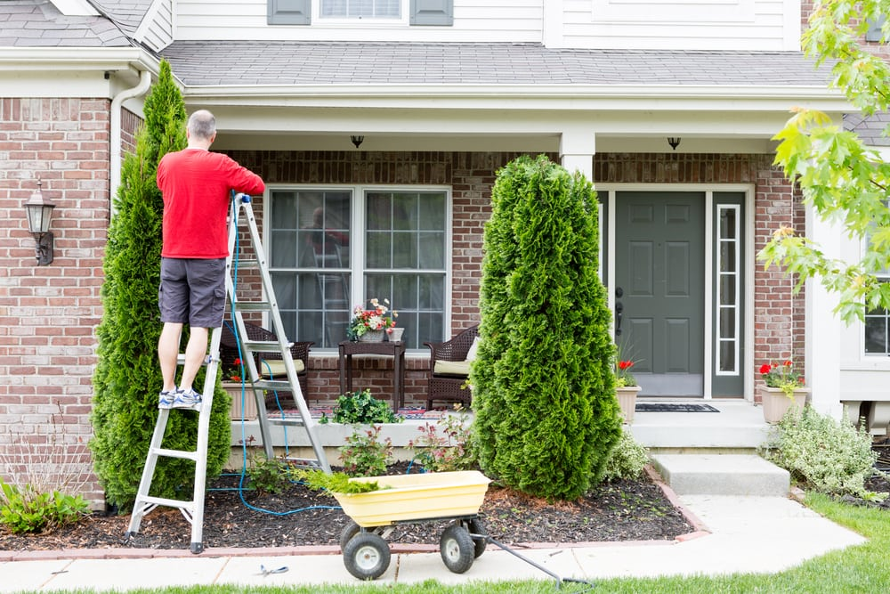 man on ladder trimming shrubs and landscape outside home