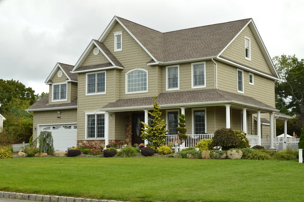 two story residential home with a freshly cut lawn