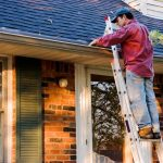 Man on Ladder Cleaning out Gutter System