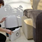 woman in living room opening up portable dehumidifier