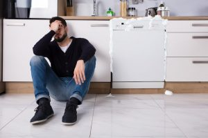 man sitting next to dishwasher with soap and water coming out