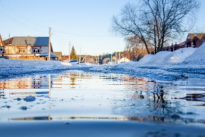 residential neighborhood with melting snowbanks and flooding