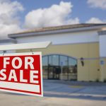 vacant commercial building with for sale sign
