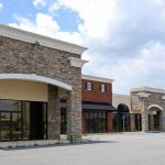 row of commercial real estate exterior store fronts and parking lot
