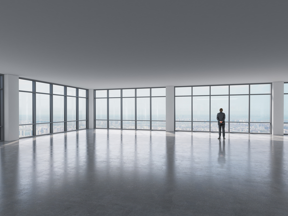 business man standing near windows in empty commercial space